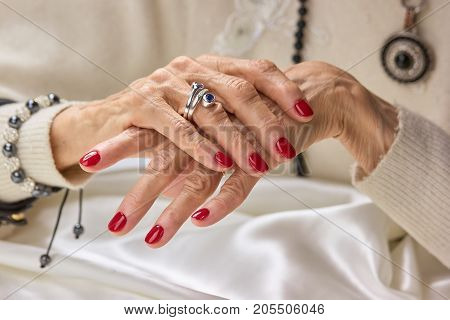Luxury female hands with red manicure. Aged woman manicured hands with beautiful silver ring. Senior aristocratic woman hands with red nails and elegant jewelry.