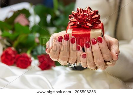 Gift box in manicured female hands. Senior woman hands with perfect red manicure holding beautiful gift box. Holidays and celebrations concept.