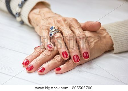 Woman manicured hands on table. Female aged hands with perfect red nails and silver luxury ring.