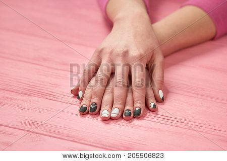 Female hands with design manicure. Girls hands with beautiful black and white matte nails on wooden table. Nails and hands care.