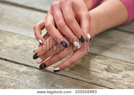Woman hands with stylish manicure. Creative black and white manicure on female hands, old wooden background.