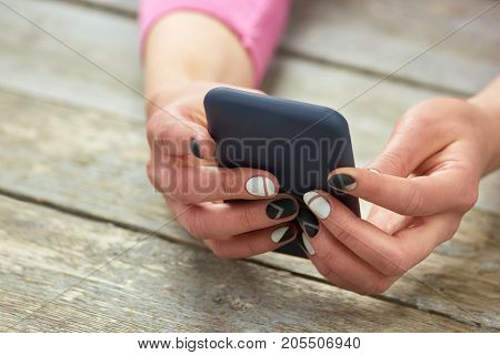 Female manicured hands with phone. Female hands with matte manicure holding a cell phone on old wooden background.