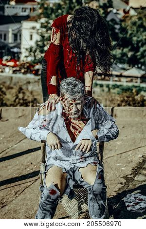 Halloween zombie couple on roof. War soldier sitting on chair. Girl with long blond hair. Man and woman with bloody wounds and red blood. Vampires in torn clothes outdoors. Holiday celebration concept