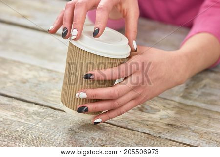 Female hands opening cardboard coffee cup. Young woman hands opening disposable cup with coffee. Time to drink coffee.