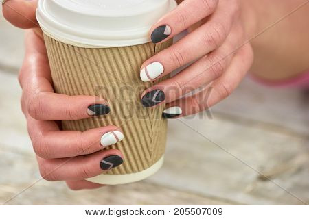 Cardboard disposable cup in female hands. Woman hands with beautiful matte manicure holding disposable cup of cappuccino. Morning starts with coffee.