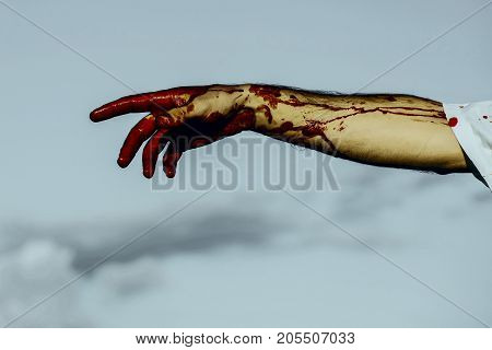 Halloween bloody hand on grey sky background. Fingers bleeding with red blood. Vampire or zombie hand. Halloween holiday celebration concept.