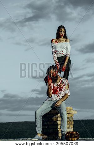 Halloween couple and pumpkin on chimney. Woman and man on grey sky. Vampires bleeding with red blood. Girl and hipster in bloody clothes on natural landscape. Halloween holiday concept