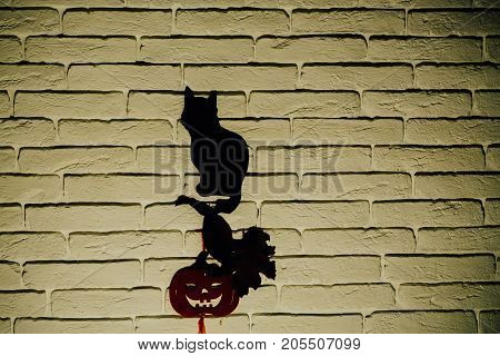Halloween totem symbols. Holiday celebration concept. Black cat and orange pumpkin with tree leaves silhouettes paper cutouts on beige brick wall. Mystery and superstition copy space