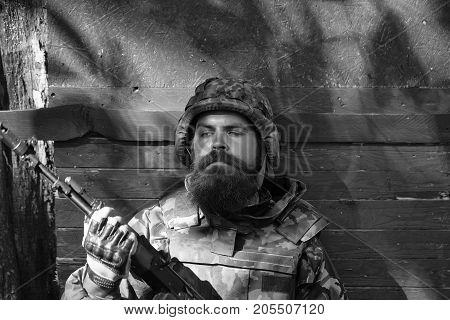 Young soldier hipster with tired bearded face in military ammunition armed with rifle in hands sitting leaned on wooden green shield