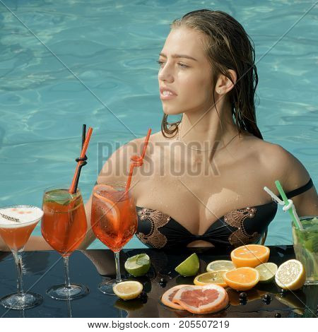 woman in pool with cocktail and fruit at summer vacation near blue water