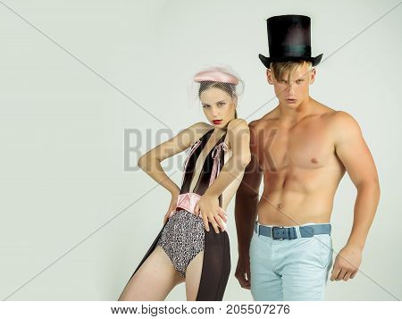 Man or macho with muscular torso in black top hat. Fitness and beauty. Fashion and style concept. Couple in love posing on grey background. Woman or girl wearing  lingerie and veil hat copy space
