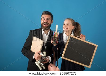 Father and schoolgirl with cheerful faces on blue background. Man and girl in school uniform. Kid and dad hold microscope blackboard book and stationery. Home schooling and back to school concept