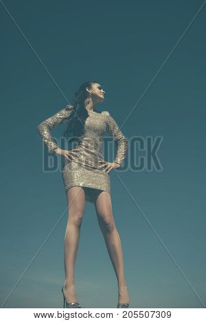 Girl in party dress with golden sequins. Woman in shoes with high heels posing on blue sky. Fashion and style. Beauty and nature. Holidays birthday new year christmas anniversary celebration