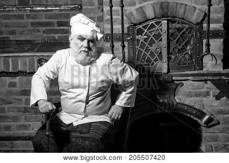Senior male chief cook bearded man in uniform and hat sits at oven on kitchen background