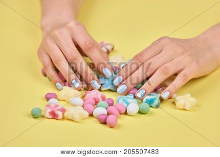 Colorful candies and woman hands. Female hands with beautiful manicure and multicolored candies on yellow background.