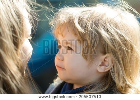Woman and child. Baby boy with long blond hair looking at mother on sunny day outdoors. Mothers day and happy childhood. Family love concept.