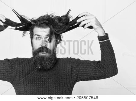 bearded man in red sweater holds fashionable black female shoes as antlers. handsome surprised guy with long hair isolated on white background