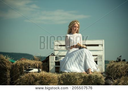Girl in straw wreath and white dress on sunny day. Summer holidays and vacation. Student with camera and typewriter on hay. Hobby and lifestyle concept. Woman reading book on bench on blue sky.