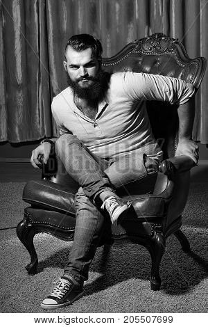 One stylish fashionable handsome brunette man with long lush beautiful beard in grey shirt and blue jeans sitting on brown leather retro chair looking forward indoor on studio background vertical pic