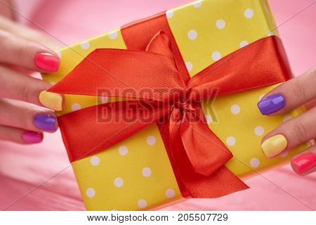 Beautiful gift box in female hands. Young woman hands with pastel color manicure holding dotted gift box close up.