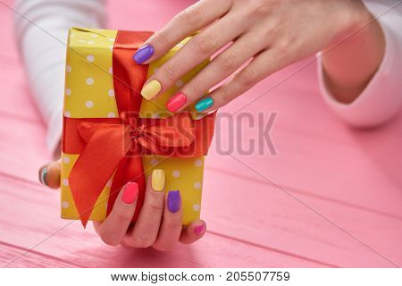 Gift box in female gentle hands. Woman hands with summer colors manicure holding yellow gift box with red bow, pink wooden background.