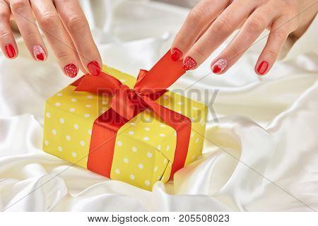 Female hands opening yellow box. Woman gentle hands unpacking yellow dotted gift box with red ribbon. Womanhood and tenderness concept.