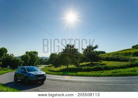 Car Driving On The Asphalt Curvy Road Through Green Fields And Forests On A Sunny Day In Normandy, F