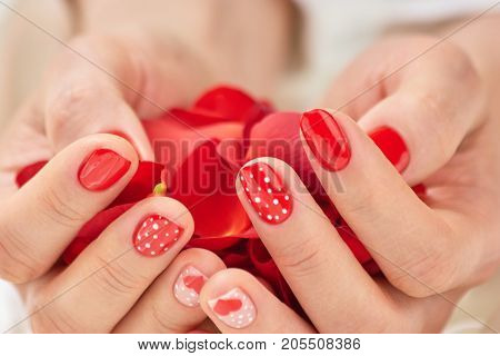 Woman hands full of red petals. Beautiful female hands with red rose petals. Romance and love concept.