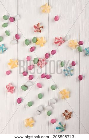 Tasty colorful candies on wooden background. Many multicolored sweet candies on white wooden background, top view.