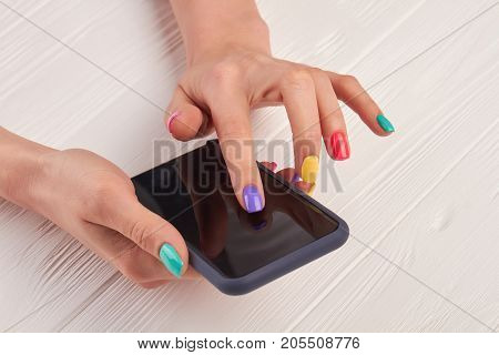 Female manicured hands with smartphone. Girl using a touch screen of smartphone on the wooden table.