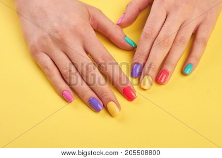 Female well-groomed hands with manicure. Young girl hands polished with different colors nail on yellow wooden background.