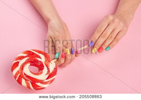Bright lollipop in female hands. Female hands with multicolor summer nails holding tasty big lollypop on pink background, top view.