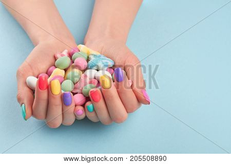 Female hands with colorful candies. Woman hands with stylish colorful nails holding multicolor candies isolated on light blue background.