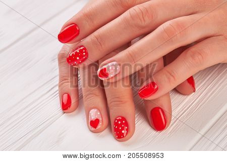Female hands with polished nails. Woman gentle hands with red hearts and dots design manicure on white wooden background close up.