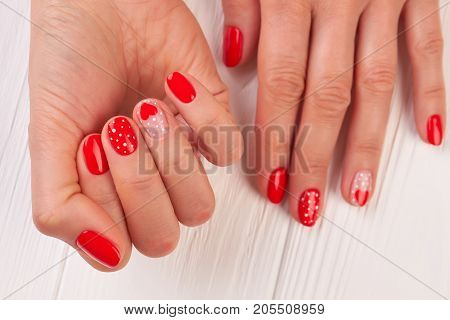 Caucasian woman manicured hands. Valentines Day Holiday bright manicure with painted hearts and dots. Female winter manicure on Valentine Day.