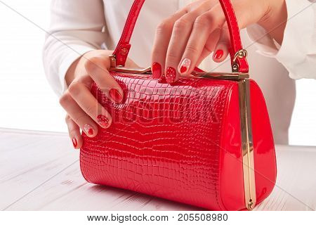 Red lacquered handbag in female hands. Stylish red handbag in female manicured hands. Woman manicured hand holding red fashion handbag.