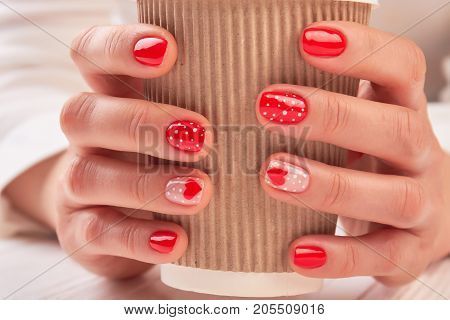 Disposable coffee cup in female hands. Woman hands with beautiful manicure holding cardboard cup with cappuccino close up.