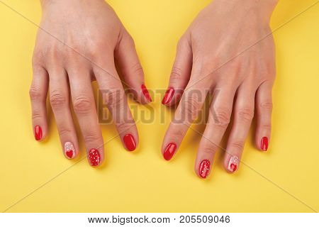 Well-groomed female hands with manicure. Young woman red manicure with painted hearts and dots islated on yellow background. Valentines day nail art design.