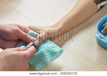 Manicurist cutting the cuticles to client. Beautician trimming cuticles to female client. Woman hands in a nail salon receiving a manicure procedure.