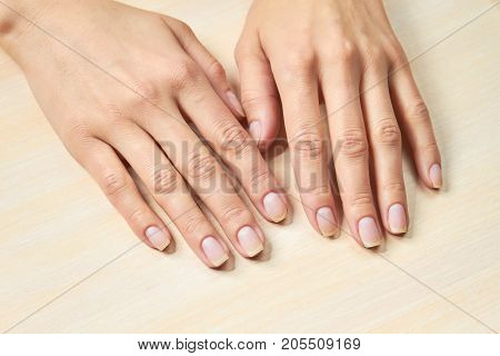 Female gentle hands. Woman beautiful hands on salon table. Woman hands in nails and spa salon.