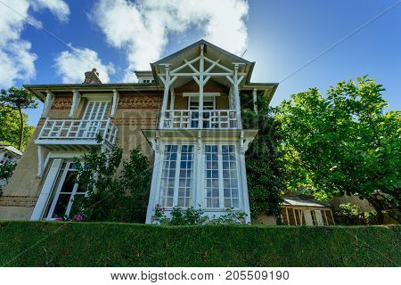 Country House With Green Fence In The Region Of Normandy, France On A Sunny Day. Beautiful Countrysi