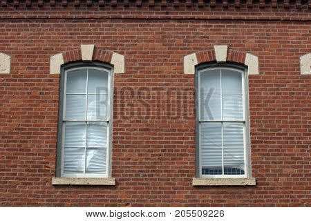 Vintage windows in red brick building with white roman shades