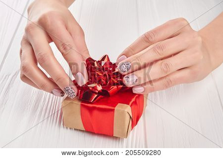 Little gift box in female manicured hands. Gentle female hands with nude patterned manicure holding handmade little gift box.