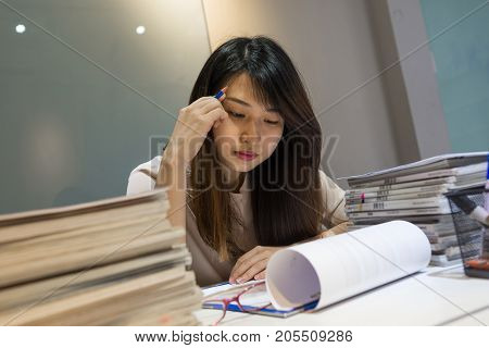 Asian employee reading sales reports carefully in her office