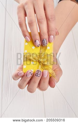 Female hands holding little gift box. Beige patterned manicure on gentle female hands. Young woman hands with beautiful gentle manicure.