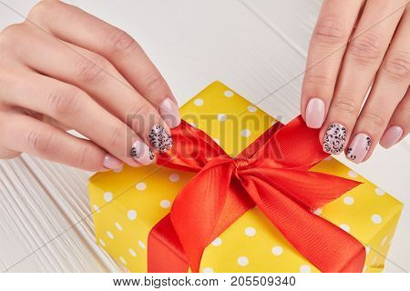 Female manicure and beautiful present. Beautiful female hands with a gift on a white wooden background. Female fingers with a manicure.