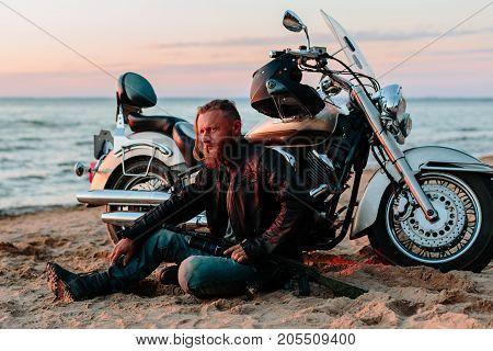 Biker and motorcycle. seashore at sunset. horizontal shot