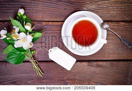 black tea in a white round cup with a saucer and an iron spoon on a brown wooden table next to a bouquet of flowering jasmine with a paper tag top view