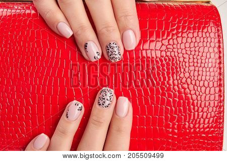 Red lacquered fashion female accessory. Well-groomed female hands with manicure holding red purse. Gentle design female manicure.