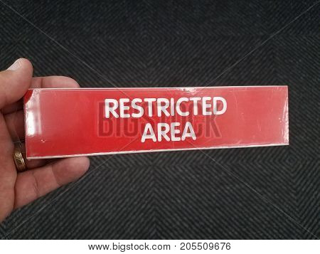 a red restricted area sign held in a hand